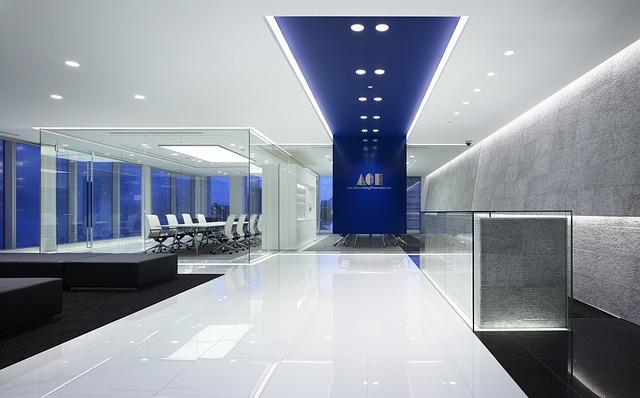moderní prostředí, lesklá podlaha na chodbě, modrý strop s výraznými světly, v dáli bílé židle ve skleněné místnosti